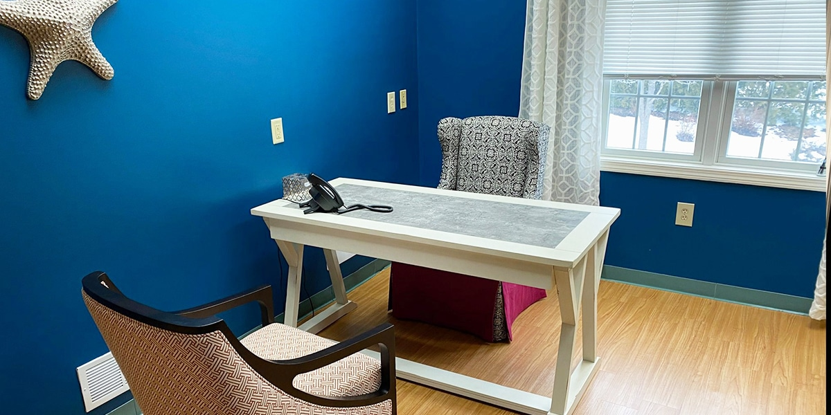white desk with chairs and white starfish on blue wall